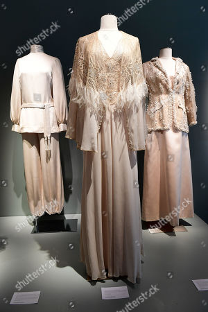 Stock Photo of A high collar blouse, matching belt, and harem pants (L), a muslin evening dress, tulle bodice and matching cape (C) and an embroidered jacket with pearls, with a long satin dress (R) from the wardrobe of Italian actress Claudia Cardinale on display at Sotheby's auction house in Paris, France, 04 July 2019. Some 130 couture and ready-to-wear creations will go on sale in a public online auction, titled 'Claudia Cardinale: Dressing a Star', at Sotheby's on 09 July 2019.