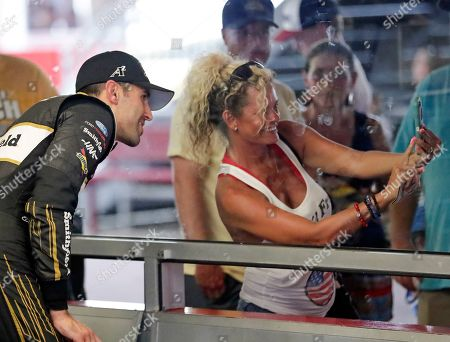 Aric Almirola, left, poses for a selfie photo in his garage with a fan during practice for the NASCAR Cup Series auto race at Daytona International Speedway, in Daytona Beach, Fla