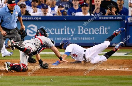 Chris Taylor, Austin Hedges, Tom Hallion. Los Angeles Dodgers' Chris Taylor, right, scores past San Diego Padres catcher Austin Hedges on a sacrifice fly by Alex Verdugo as home plate umpire Tom Hallion watches during the fifth inning of a baseball game, in Los Angeles