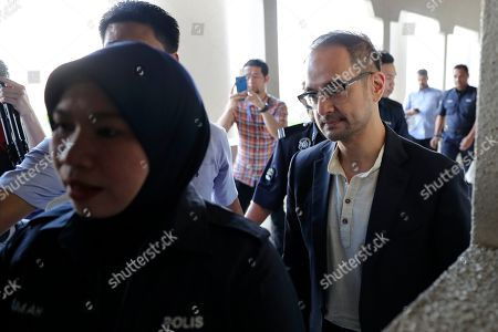 Riza Aziz, right, stepson of Malaysian former Prime Minister Najib Razak, walks into a court room at Kuala Lumpur High Court in Kuala Lumpur, Malaysia, . Malaysia's anti-graft agency said Thursday it has detained Riza Aziz, the stepson of ex-premier Najib Razak and a Hollywood film producer, and will charge him with money laundering