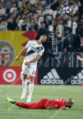 LA Galaxy defender Giancarlo Gonzalez (21) heads the ball as Toronto FC goalkeeper Alex Bono (25) falls during an MLS soccer match in Carson, Calif., . The Galaxy won 2-0