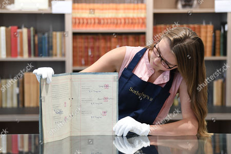 An auction worker holds the 1962 original and first management contract between members of The Beatles and English music entrepreneur Brian Epstein, which was signed by John Lennon, Paul McCartney, George Harrison and Pete Best at a preview of the sale of English Literature, History Children's Books and Illustrations at Sotheby's auction house in London, Britain, 05 July 2019. The online bidding closes on 09 July.