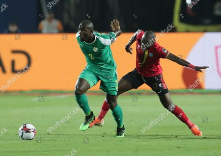 Senegal's Saliou Ciss in action in front of Uganda's Emmanuel Arnold okwi during the African Cup of Nations round of 16 soccer match between Uganda and Senegal in Cairo International stadium in Cairo, Egypt