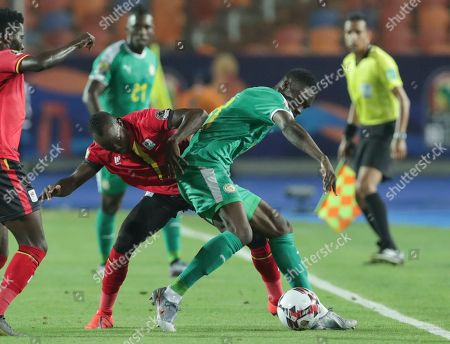 Uganda's Godfrey Walusimbi, left, and Senegal's Ismaila Sarr fight for the ball during the African Cup of Nations round of 16 soccer match between Uganda and Senegal in Cairo International stadium in Cairo, Egypt