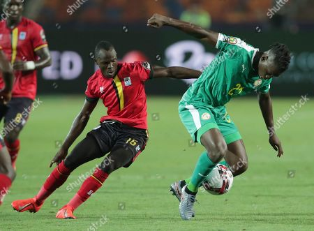 Uganda's Godfrey Walusimbi, left, and Senegal's Lamine Gassama fight for the ball during the African Cup of Nations round of 16 soccer match between Uganda and Senegal in Cairo International stadium in Cairo, Egypt