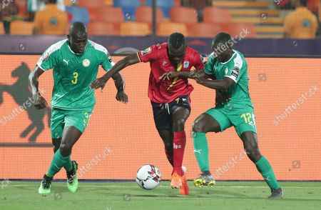 Uganda's Emmanuel Arnold okwi in action between Senegal's Kalidou Koulibaly, left, and Youssouf Sabaly during the African Cup of Nations round of 16 soccer match between Uganda and Senegal in Cairo International stadium in Cairo, Egypt