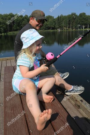"Alaska Heat Wave. Tessa King, 4, tries catching a fish for first time with her father, Shawn King,, at Jewel Lake in Anchorage, Alaska. She took off her shoes and proclaimed, ""It's too hot to wears shoes."" The official temperature on Thursday, July 4, reached 90 degrees for the first time in Anchorage and hot weather is expected to continue into next week"