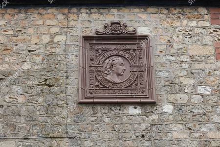Plaque on flint stone cottage wall marking sixty years of Queen Victoria being Empress of India