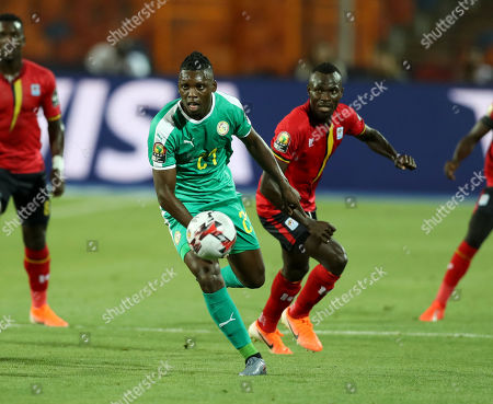 Lamine Gassama (C) of Senegal challenged by Emmanuel Okwi (R0 of Uganda during the 2019 Africa Cup of Nations (AFCON 2019) round of 16 soccer match between Uganda and Senegal in Cairo Stadium in Cairo, Egypt, 05 July 2019.