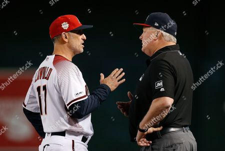 Arizona Diamondbacks manager Torey Lovullo, left, argues with umpire Bill Miller, right, after Miller called Diamondbacks' Zack Greinke for interference during the third inning of a baseball game against the Colorado Rockies, in Phoenix