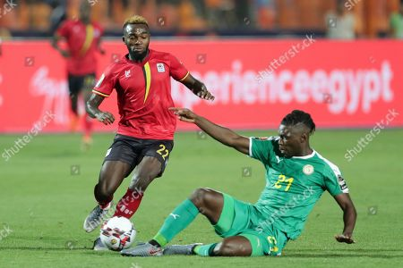 Uganda's Abdu Lumala, left, fights for the ball with Senegal's Lamine Gassama during the African Cup of Nations round of 16 soccer match between Uganda and Senegal in Cairo International stadium in Cairo, Egypt