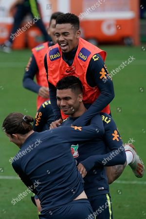Brazil's Casimiro, center, Filipe Luis and Gabriel Jesus, top, joke around as they take part in a practice session at the Granja Comary training center in Teresopolis, Brazil, . Brazil will face Peru for the Copa America final soccer match on July 7