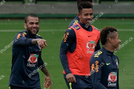 Brazil's Daniel Alves, left, Gabriel Jesus, center, and David Neres, joke around as they take part in a practice session at the Granja Comary training center in Teresopolis, Brazil, . Brazil will face Peru for the Copa America final soccer match on July 7