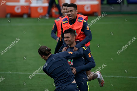 Stock Photo of Brazil's Casimiro, center, Filipe Luis and Gabriel Jesus, top, joke around as they take part in a practice session at the Granja Comary training center in Teresopolis, Brazil, . Brazil will face Peru for the Copa America final soccer match on July 7