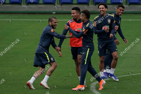Brazil's Daniel Alves, left, Gabriel Jesus, center and David Neres, joke around as they take part in a practice session at the Granja Comary training center in Teresopolis, Brazil, . Brazil will face Peru for the Copa America final soccer match on July 7