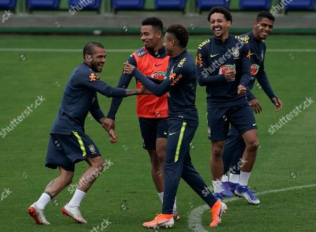 Brazil's Daniel Alves, left, Gabriel Jesus, center, and David Neres, joke during a practice session at the Granja Comary training center in Teresopolis, Brazil, . Brazil will face Peru for the Copa America final soccer match on July 7