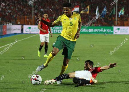 Egypt's Ayman Ashraf clears the ball in frotn of South Africa's Bongani Zungu during the African Cup of Nations round of 16 soccer match between Egypt and South Africa in Cairo International stadium in Cairo, Egypt