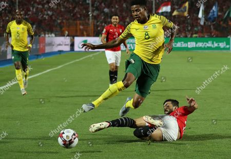 Stock Image of Egypt's Ayman Ashraf clears the ball in frotn of South Africa's Bongani Zungu during the African Cup of Nations round of 16 soccer match between Egypt and South Africa in Cairo International stadium in Cairo, Egypt