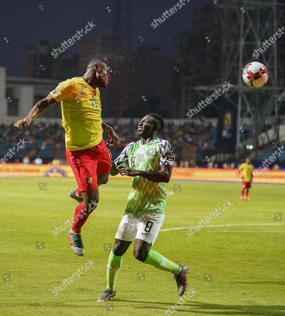 FRANCE OUT Christian Mougang Bassogog of Cameroon heading the ball in front of oghenekaro Peter Etebo of Nigeria during the African Cup of Nations match between Cameroon and Nigeria at the Alexanddria Stadium in Alexandria, Egypt