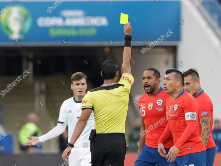 Referee Mario Diaz of Paraguay shows the yellow card to Chile's Jean Beausejour (15) during Copa America third-place soccer match at the Arena Corinthians in Sao Paulo, Brazil