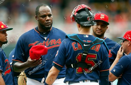 Miguael Pineda, Wes Johnson, Jason Castro. Minnesota Twins pitcher Michael Pineda, left, holds his cap as he gets a mound visit from catcher Jason Castro and pitching coach Wes Johnson, right, after giving up a walk to load the bases against the Texas Rangers in the third inning of a baseball game, in Minneapolis