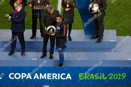 Chile's Jean Beausejour, center, collects the fourth place trophy after the Copa America third-place soccer match against Argentina at the Arena Corinthians in Sao Paulo, Brazil,. Argentina won the match 2-1