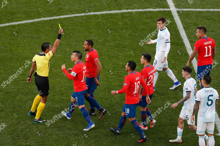 Stock Picture of Referee Mario Diaz, left, shows a yellow card to Chile's Jean Beausejour third from left, during the Copa America third-place soccer match against Argentina at the Arena Corinthians in Sao Paulo, Brazil