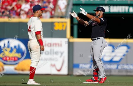 Cleveland Indians' Bobby Bradley celebrates a double off Cincinnati Reds relief pitcher Matt Bowman during the ninth inning of a baseball game, in Cincinnati. At left is Reds shortstop Jose Iglesias