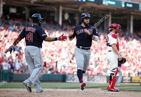Cleveland Indians' Carlos Santana (41) and Jason Kipnis slaps hands after scoring on a single by Jake Bauers off Cincinnati Reds relief pitcher Matt Bowman during the ninth inning of a baseball game, in Cincinnati. At right is Reds catcher Curt Casali