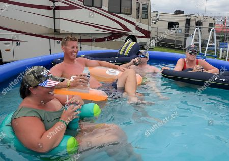 Race fans, from left to right, Lauren Hopkins, J.D. Johnson, Aaron Hopkins and Michelle Johnson cool off in a pool in the infield before a NASCAR Cup Series auto race at Daytona International Speedway, in Daytona Beach, Fla