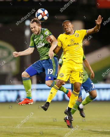 Seattle Sounders' Harry Shipp, left, heads the ball away from Columbus Crew's Robinho during the second half of an MLS soccer match, in Columbus, Ohio. The Sounders won 2-1