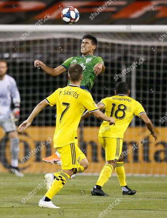 Seattle Sounders' Xavier Arreaga, top, heads the ball near Columbus Crew's Pedro Santos, left, and Robinho during the second half of an MLS soccer match, in Columbus, Ohio. The Sounders won 2-1