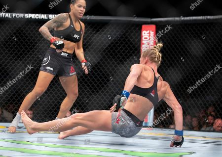 Amanda Nunes, left, knocks out Holly Holm with a kick during the first round of their women's bantamweight mixed martial arts title bout at UFC 239, in Las Vegas