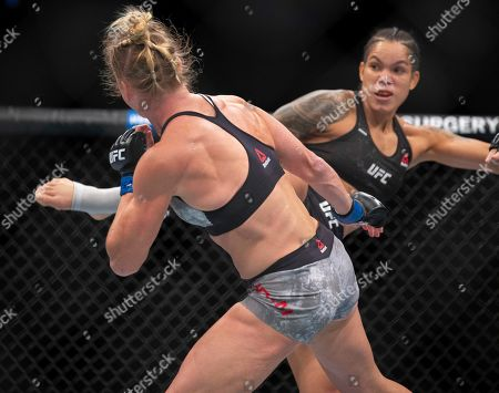 Amanda Nunes, right, knocks out Holly Holm with a kick during the first round of their women's bantamweight mixed martial arts title bout at UFC 239, in Las Vegas. Nunes won by knockout
