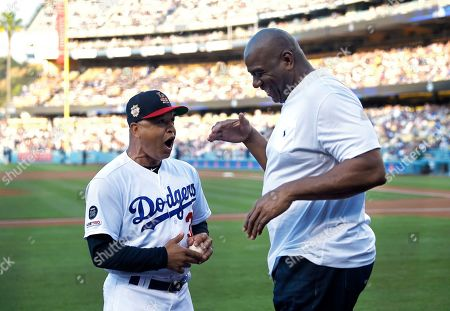 """Stock Picture of Dave Roberts, Magic Johnson. Los Angeles Dodgers manager Dave Roberts, left, talks with Dodgers co-owner Earvin """"Magic"""" Johnson prior to the team's baseball game against the San Diego Padres, in Los Angeles"""