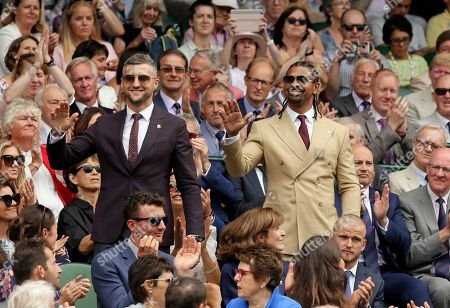 Former world champion boxers Carl Froch and David Haye, right, stand up after being introduced to the crowd on Centre Court during day six of the Wimbledon Tennis Championships in London