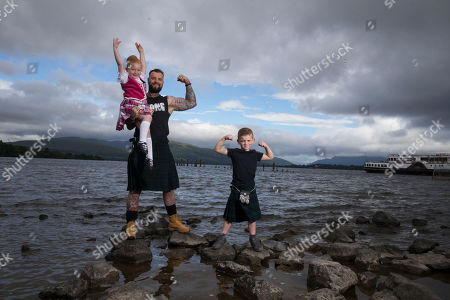 Stock Photo of A Balloch schoolboy flexed his muscle with one of West Dunbartonshire's strongest men as this year's Highland Games was officially launched this week. Young Jack, 5, showed heavyweight Thomas Graham what he was made of for one of the event's most popular competitions ' tossing the caber.... The pair were joined by dancers Kristie Scott, 14, and Ella Potter, 5, both from Lacey Brown School of Dance, who will compete in the Highland dancing competition.