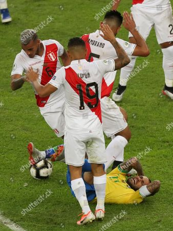 Brazil's Dani Alves falls surrounded by Peru's players Yoshimar Yotun (19). Miguel Angel Trauco,left, and Miguel Araujo during the final soccer match of the Copa America at the Maracana stadium in Rio de Janeiro, Brazil