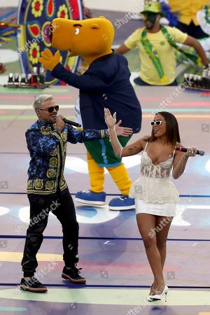 Anitta, left, and Pedro Capo sing prior to the final soccer match of the Copa America between Brazil and Peru at the Maracana stadium in Rio de Janeiro, Brazil