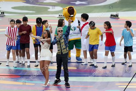 Anitta, left, and Pedro Capo, of Puerto Rico, sing prior to the final soccer match of the Copa America between Brazil and Peru at the Maracana stadium in Rio de Janeiro, Brazil