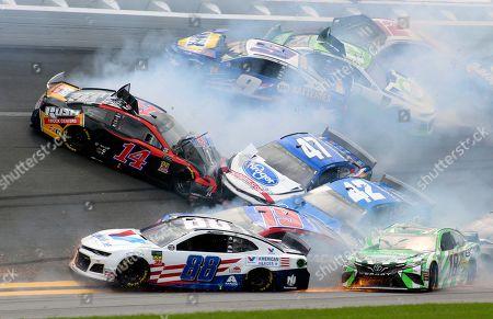 Clint Bowyer (14), Alex Bowman (88), Kyle Busch (18), Kyle Larson (42), Ryan Preece (47), Martin Truex Jr. (19), Chase Elliott (9), Austin Dillon (3) and Ryan Blaney (12) get caught up in a multi-car crash in Turn 1 during a NASCAR Cup Series auto race at Daytona International Speedway, in Daytona Beach, Fla
