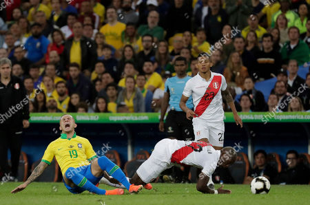Brazil's Everton, left, reacts after being fouled by Peru's Luis Advincula during the final soccer match of the Copa America at Maracana stadium in Rio de Janeiro, Brazil
