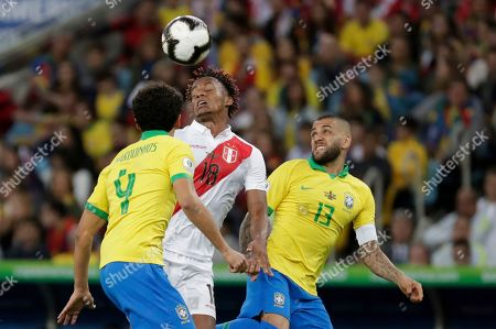 Peru's Andre Carrillo, center, battles for the ball between Brazil's Dani Alves, right, and Marquinhos during the final match of the Copa America soccer tournament at Maracana stadium in Rio de Janeiro, Brazil