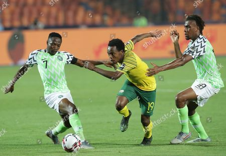 Nigeria players  Ahmed Musa (L) and  Alexander Iwobi (R) in action against South Africa's Percy Tau (C) during the 2019 Africa Cup of Nations (AFCON) quarter final soccer match between Nigeria and South Africa in Cairo, Egypt, 10 July 2019.