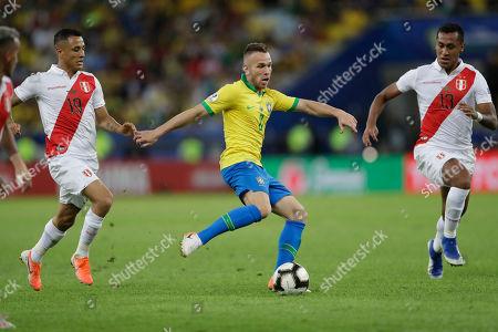 Brazil's Arthur, center, kicks the ball between Peru's Yoshimar Yotun, left, and Renato Tapia during the final match of the Copa America at the Maracana stadium in Rio de Janeiro, Brazil