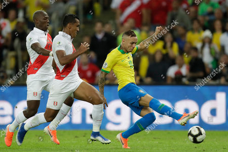 Brazil's Everton, right, strikes the ball followed by Peru's Renato Tapia, center, and Luis Advincula during the final match of the Copa America at the Maracana stadium in Rio de Janeiro, Brazil