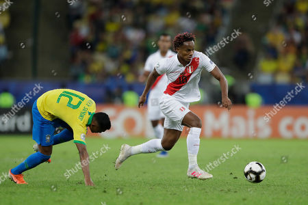 Peru's Andre Carrillo, center, dribbles the ball past Brazil's Alex Sandro during the final match of the Copa America at the Maracana stadium in Rio de Janeiro, Brazil