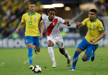 Peru's Andre Carrillo, center, goes for the ball followed by Brazil's Casemiro, right, during the final match of the Copa America at the Maracana stadium in Rio de Janeiro, Brazil