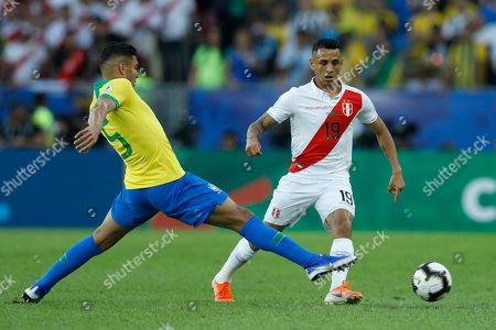 Brazil's Casemiro, left, fights for the ball with Peru's Yoshimar Yotun during the final soccer match of the Copa America at the Maracana stadium in Rio de Janeiro, Brazil