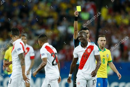 Referee Roberto Tobar shows the red card to Peru's Luis Advincula (17) during the final soccer match of the Copa America against Brazil at the Maracana stadium in Rio de Janeiro, Brazil